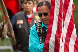 Ground Blessing Ceremony photo of man with flag web.jpg